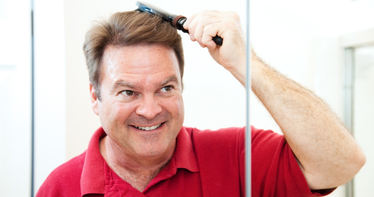 middle aged american man brushing hair smiling