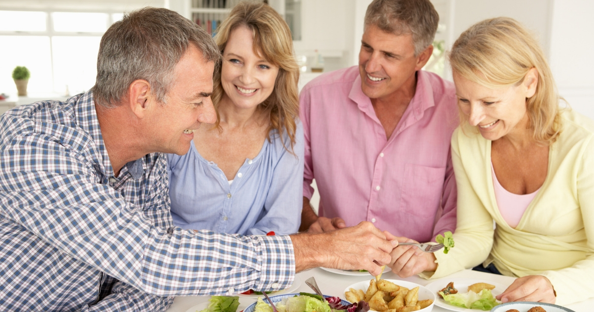 middle aged friends sharing food over table