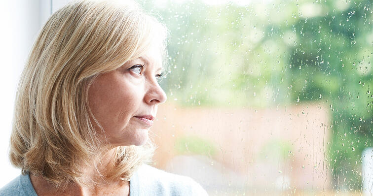 middle aged woman looking out window