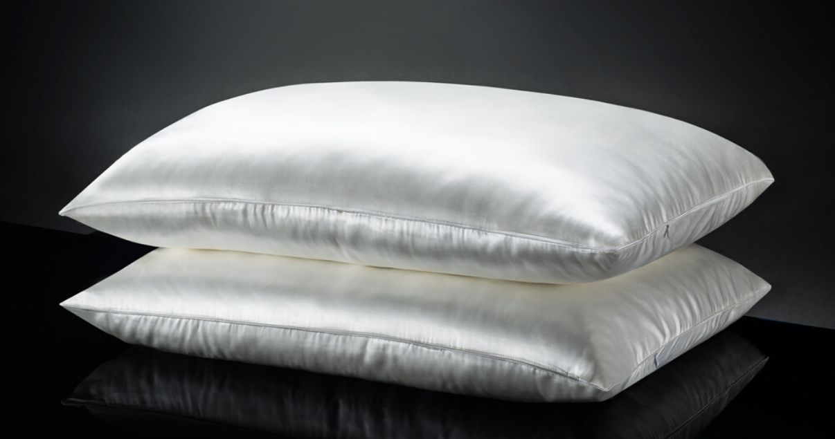 white silk pillows against black background good for sleeping in hairpiece