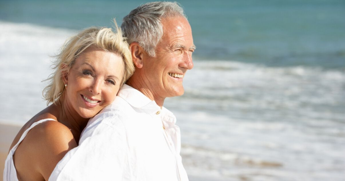 mature couple on beach preventing oxidation by taking hair system care precautions