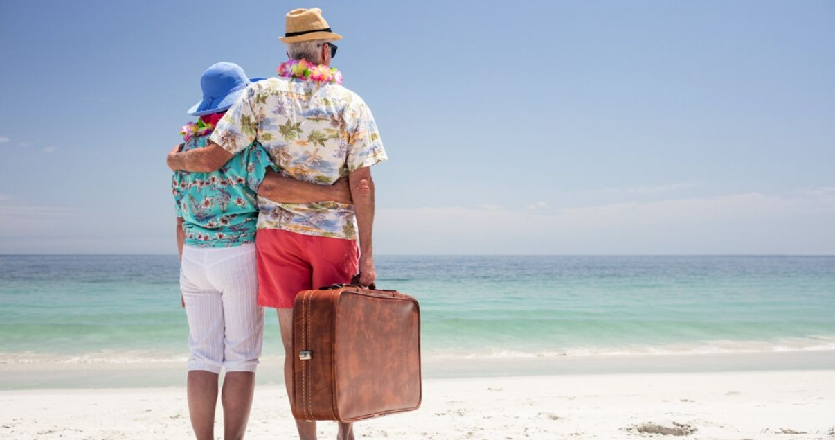 mature couple traveling with hairpieces at the beach on vacation