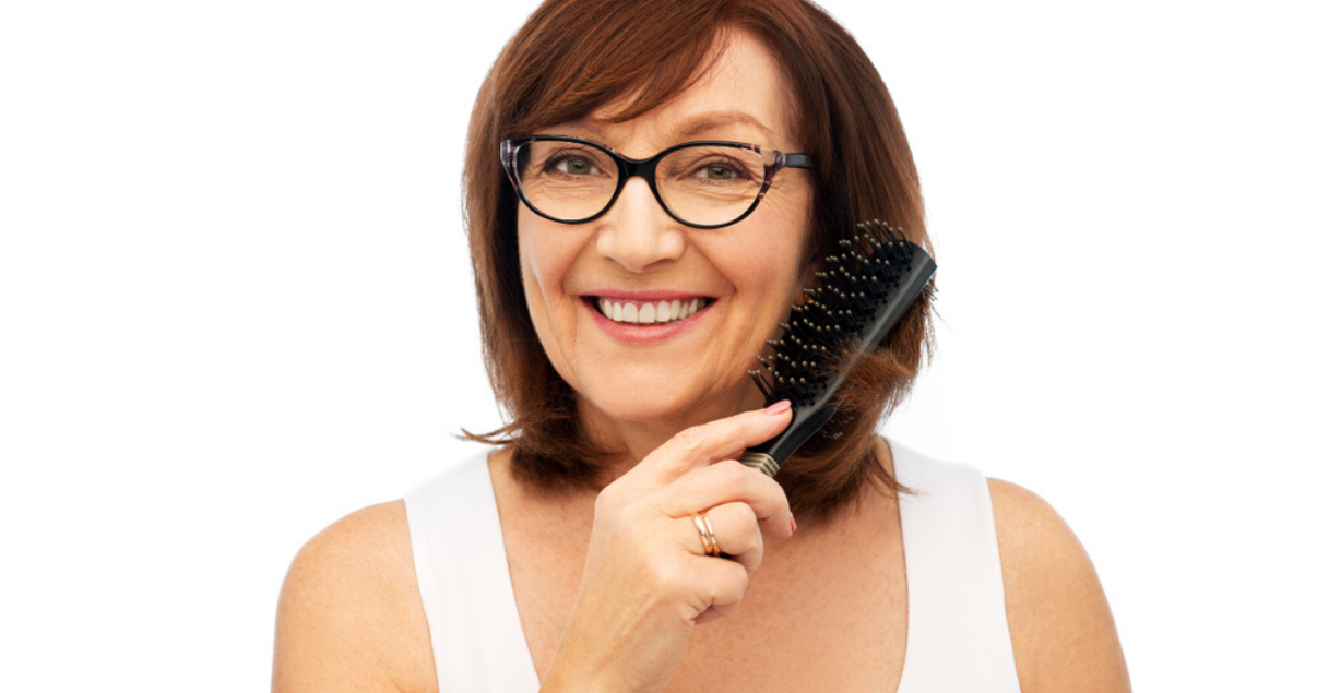mature woman changing her hair system style with a brush