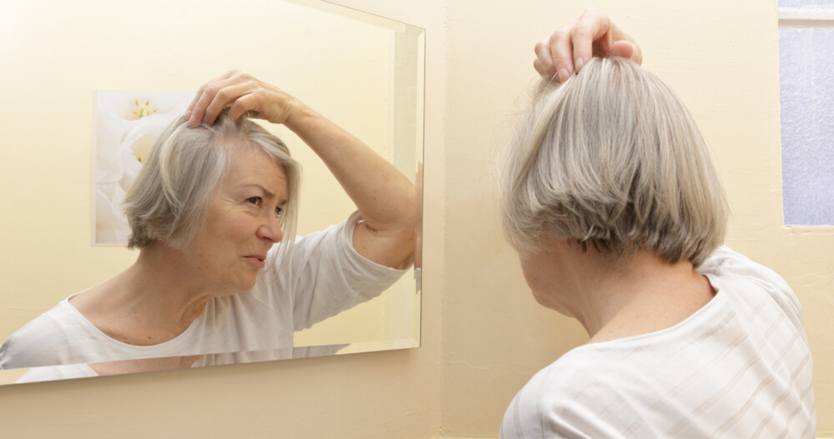 mature woman following scalp maintenance advice by massaging scalp and applying soothing oil