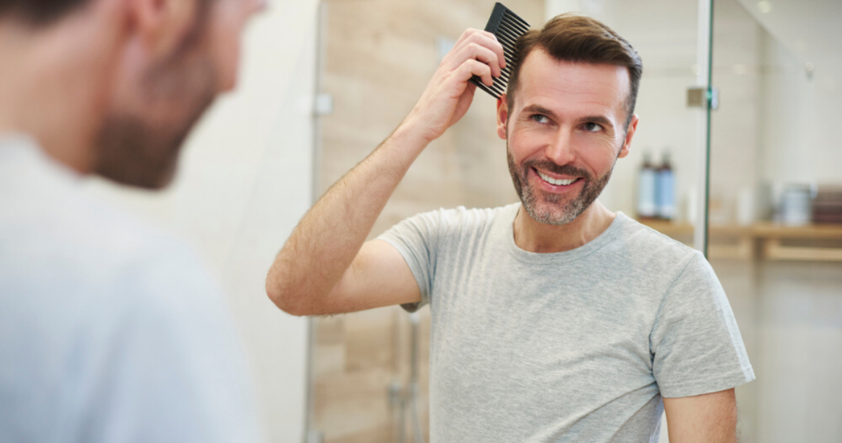 Man combing stock hairpiece in bathroom