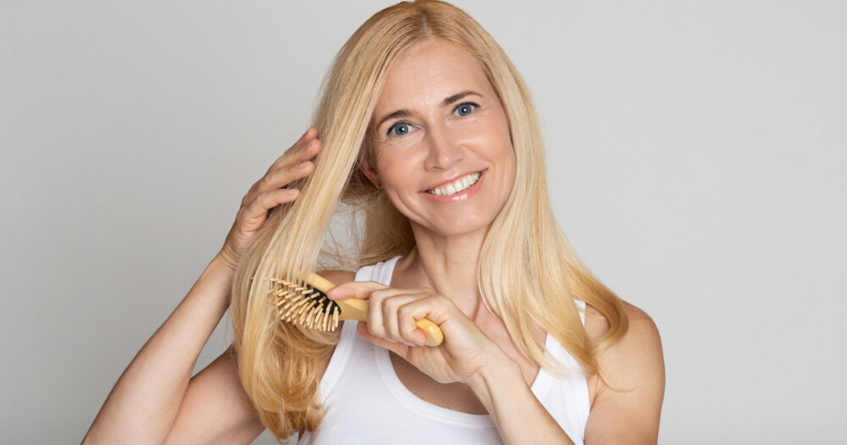 Middle aged woman brushing stock hairpiece