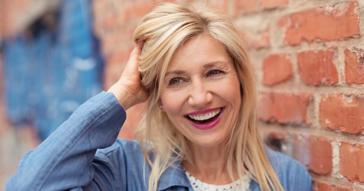 mature woman touching remy stock hairpiece hair system cleaned using hairpiece maintenance techniques