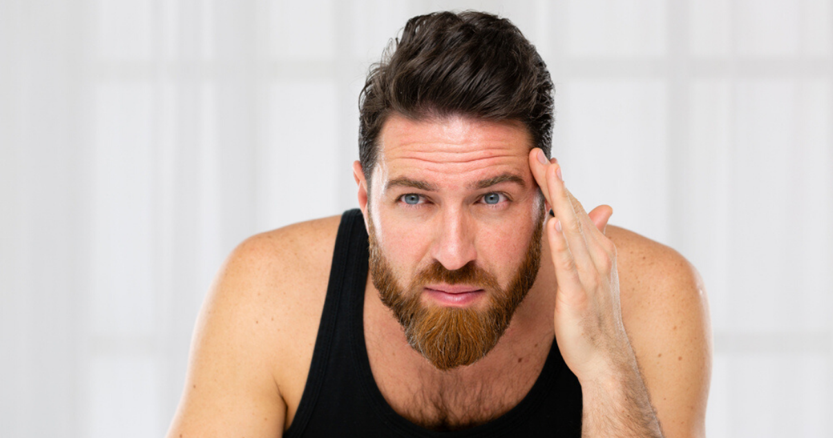 middle aged man using hairpiece maintenance techniques to bond front hairline