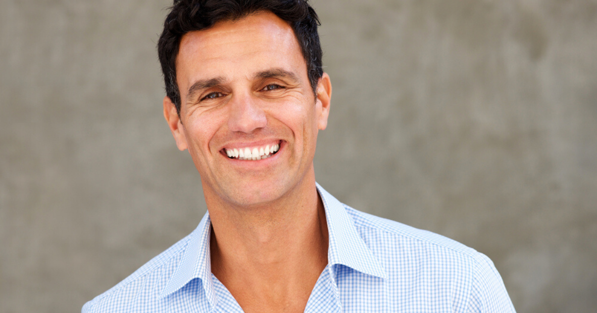 Smiling mature man wearing hair system maintained with proper hairpiece care (1)