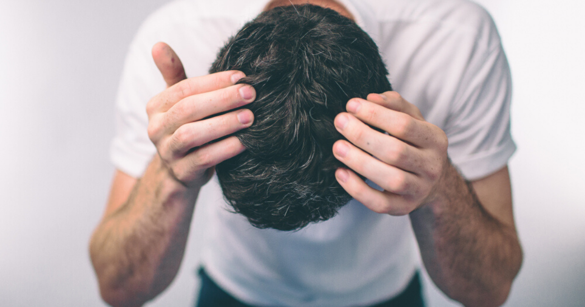 middle aged man applying hairpiece after preparing scalp