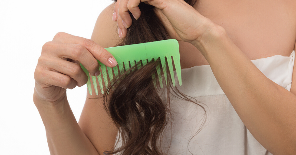 Woman combing hairpiece for good hair system care