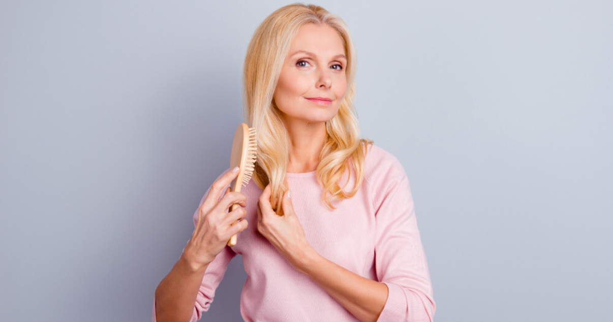 Mature woman improving hair system lifespan by maintaining it