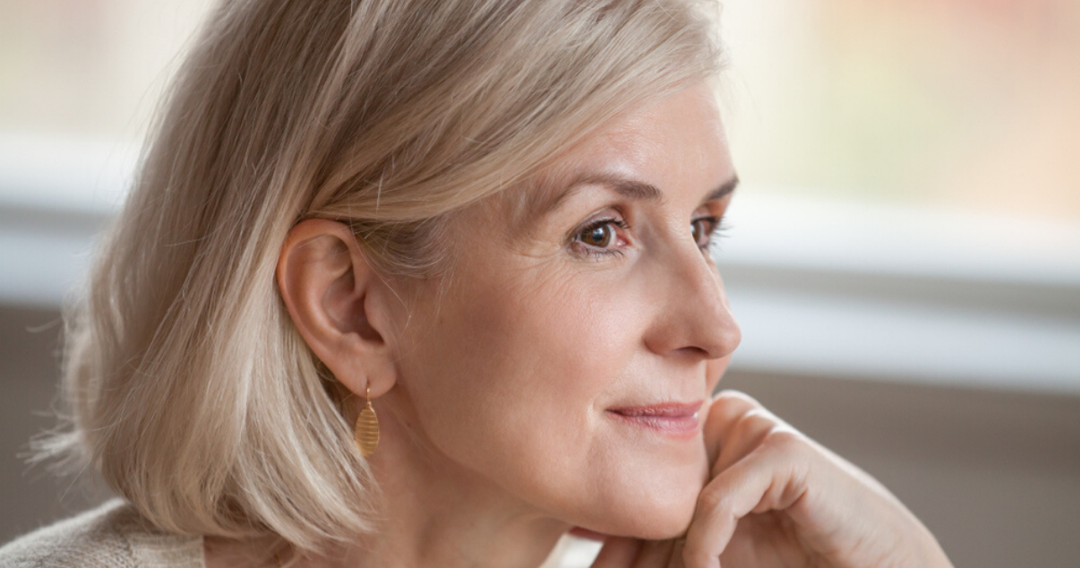Middle aged woman wearing hairpiece that she cleaned using hairpiece maintenance steps