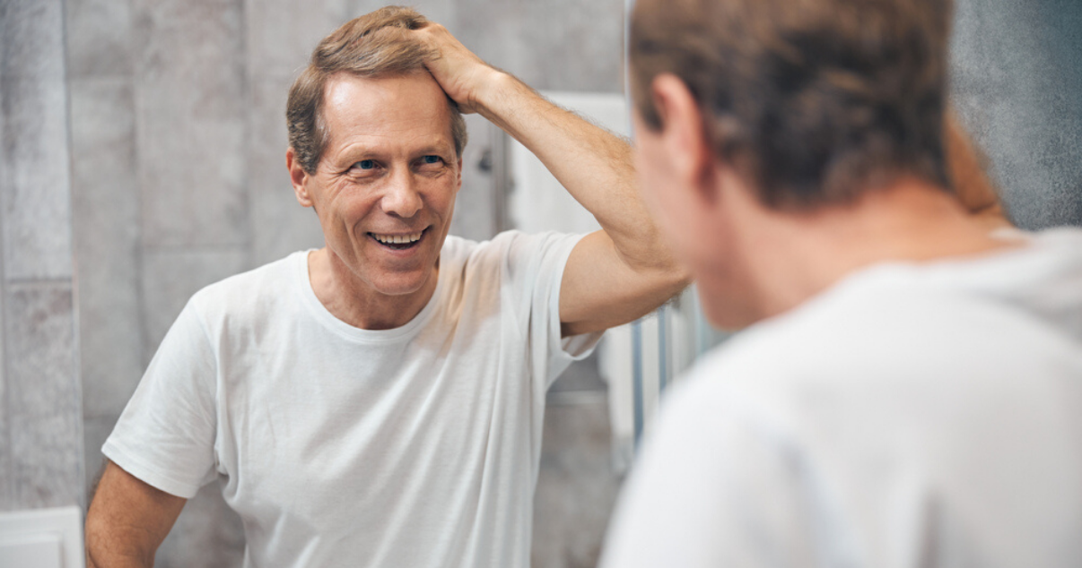 Middle aged man performing at home hair system application