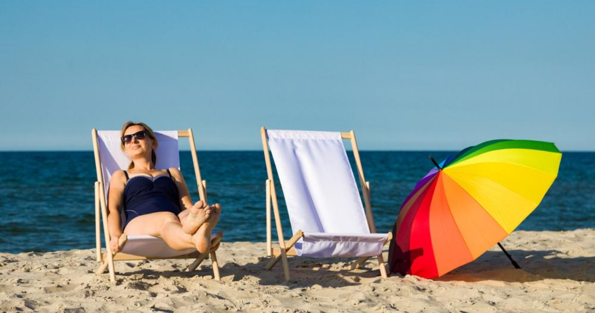Middle aged woman relaxing on beach with good hair system maintenance
