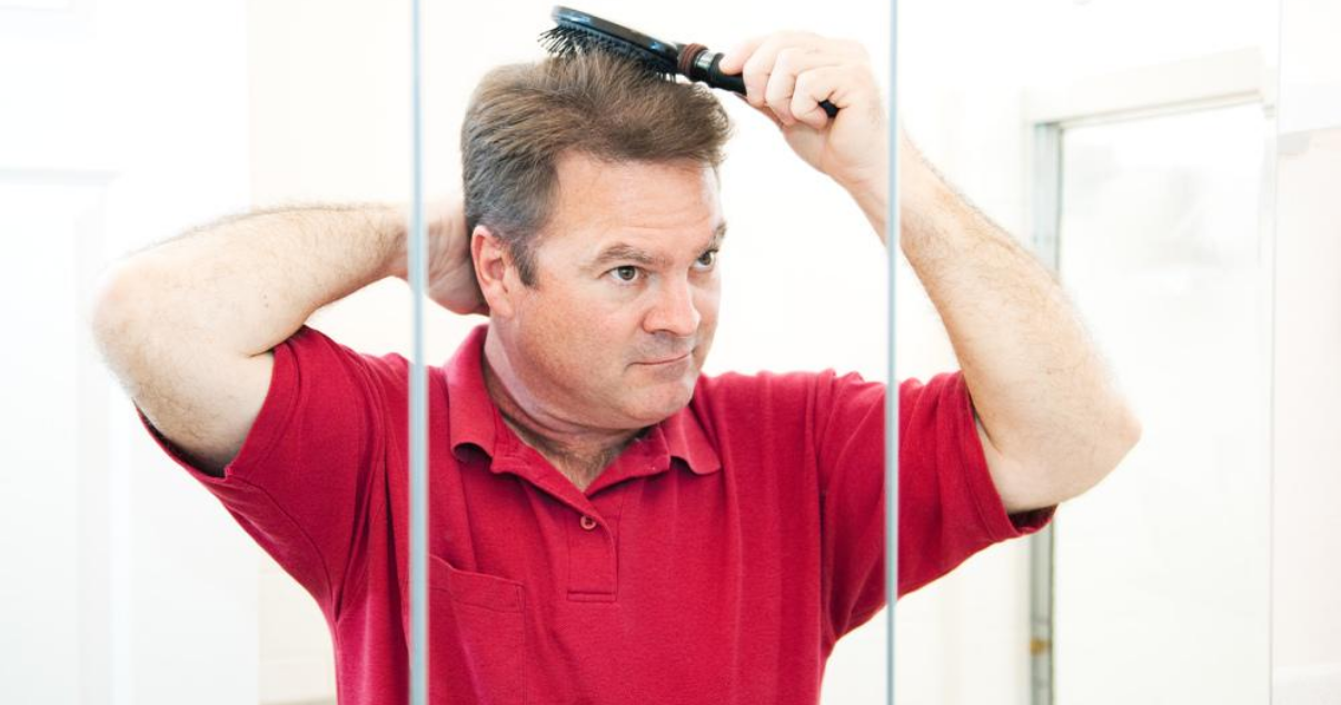 Mature man doing hair system maintenance at home without a hair club
