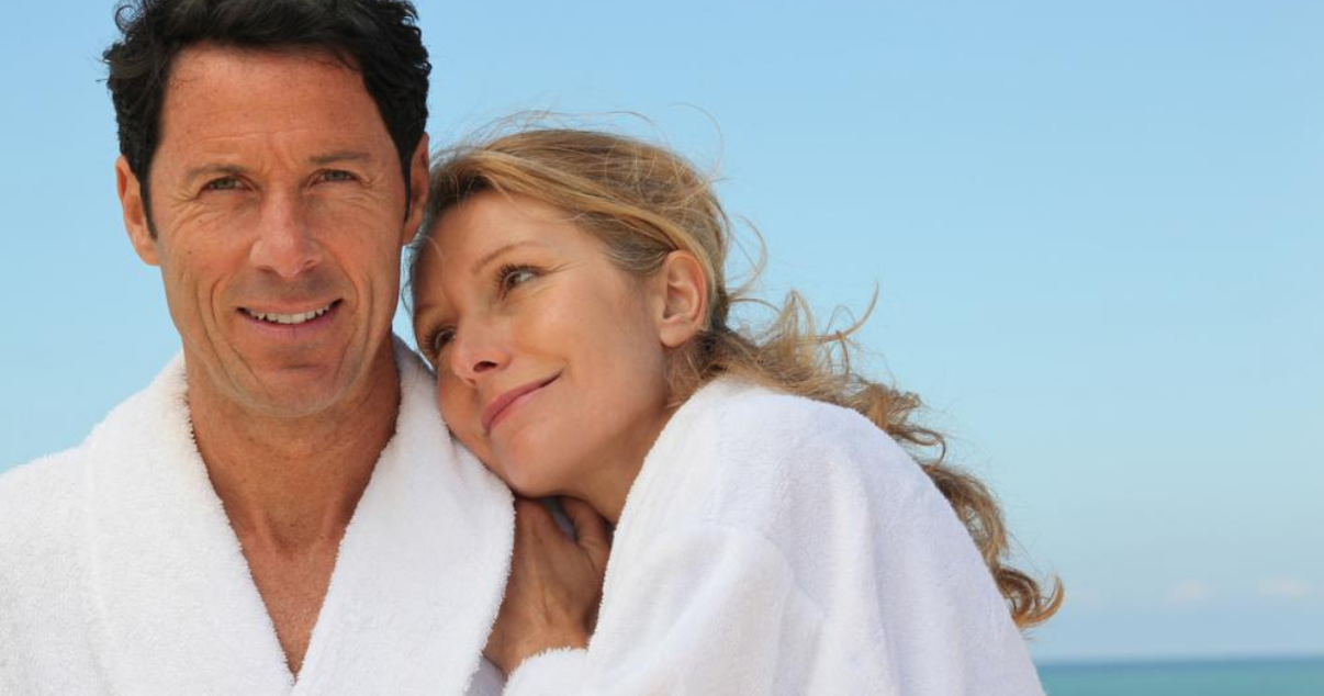 Middle aged couple on the beach with hair systems without hair club