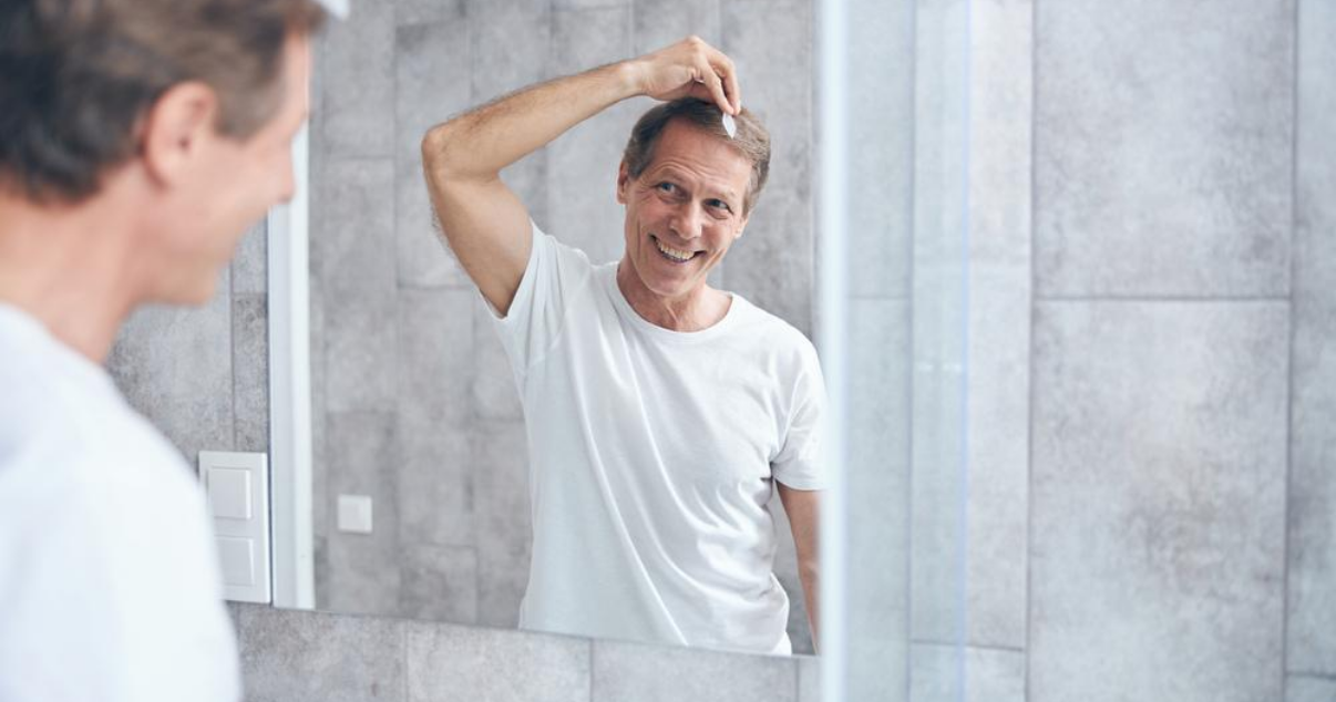Older man doing hair system attachment at home without using hair club
