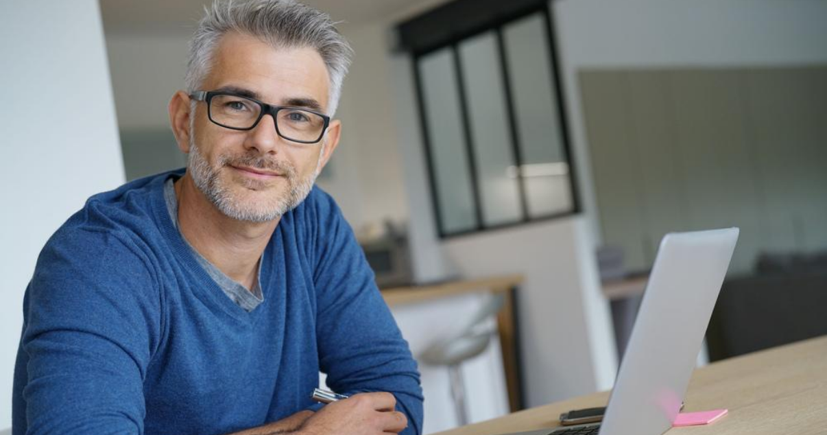 Middle aged man working from home using hair systems for men
