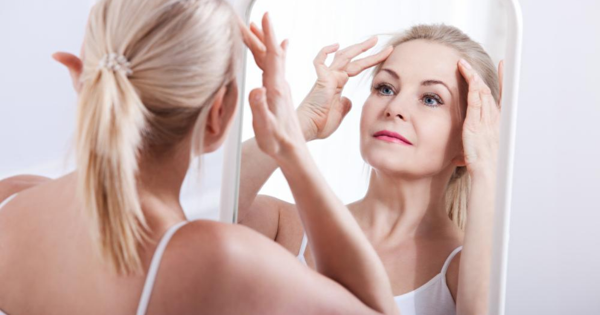 Middle aged woman in bathroom prolonging hair system lifespan