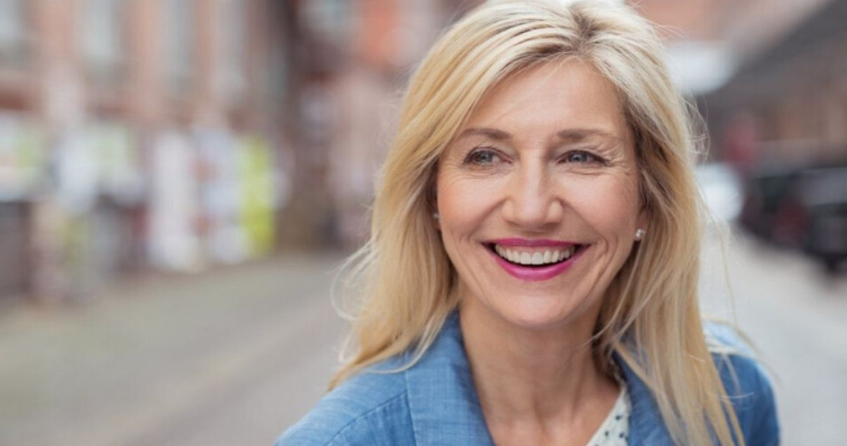 mature woman happy with her hair system after removing hairpiece adhesive buildup