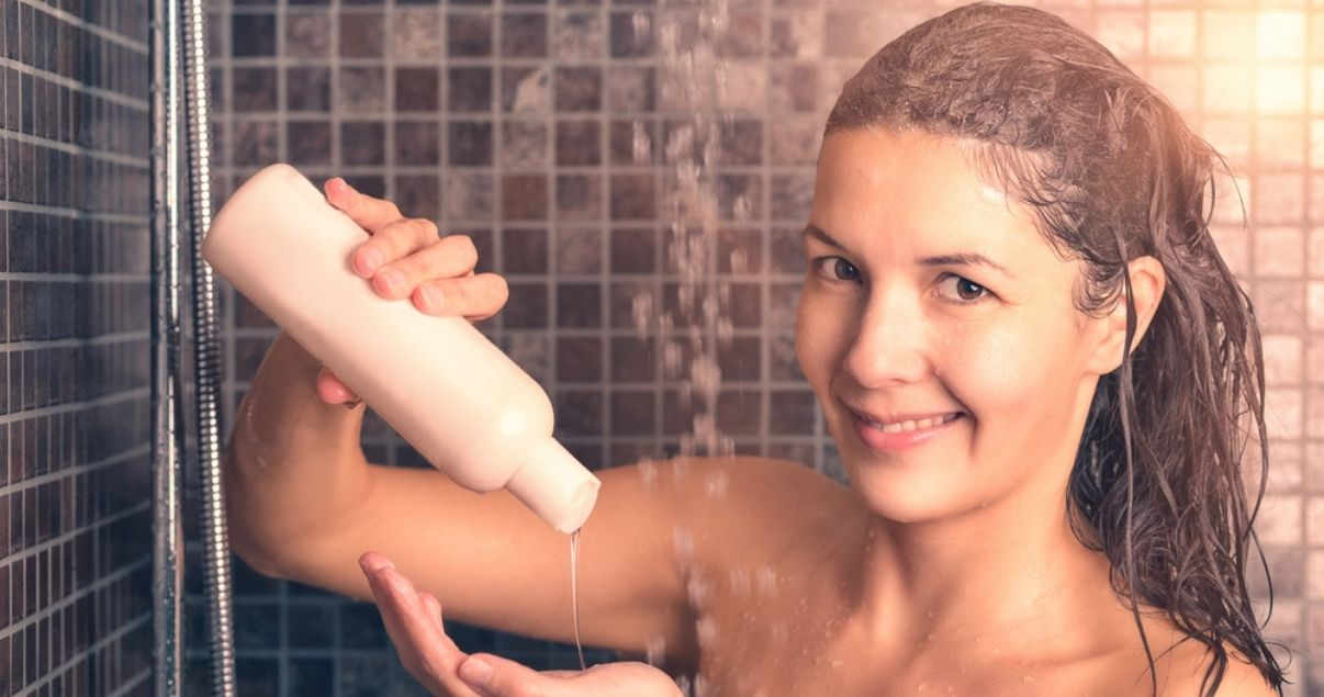 Middle aged brunette woman using shampoo for wigs