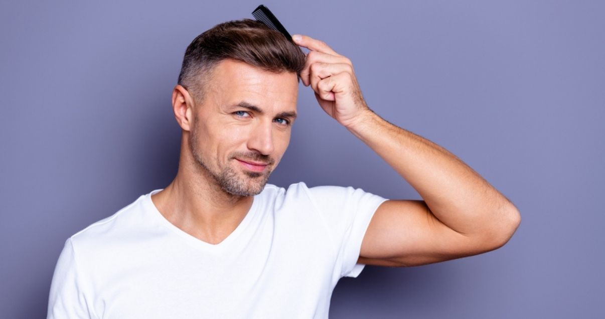 Middle aged man combing hair after using shampoo for wigs