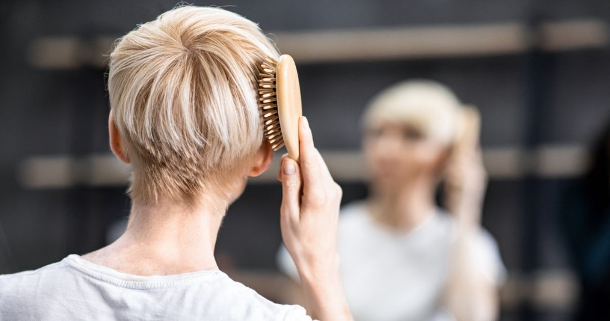 Middle aged woman brushing hair after using shampoo for wigs