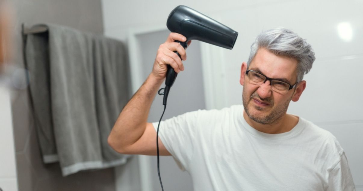 Middle aged man using blow dryer on wig