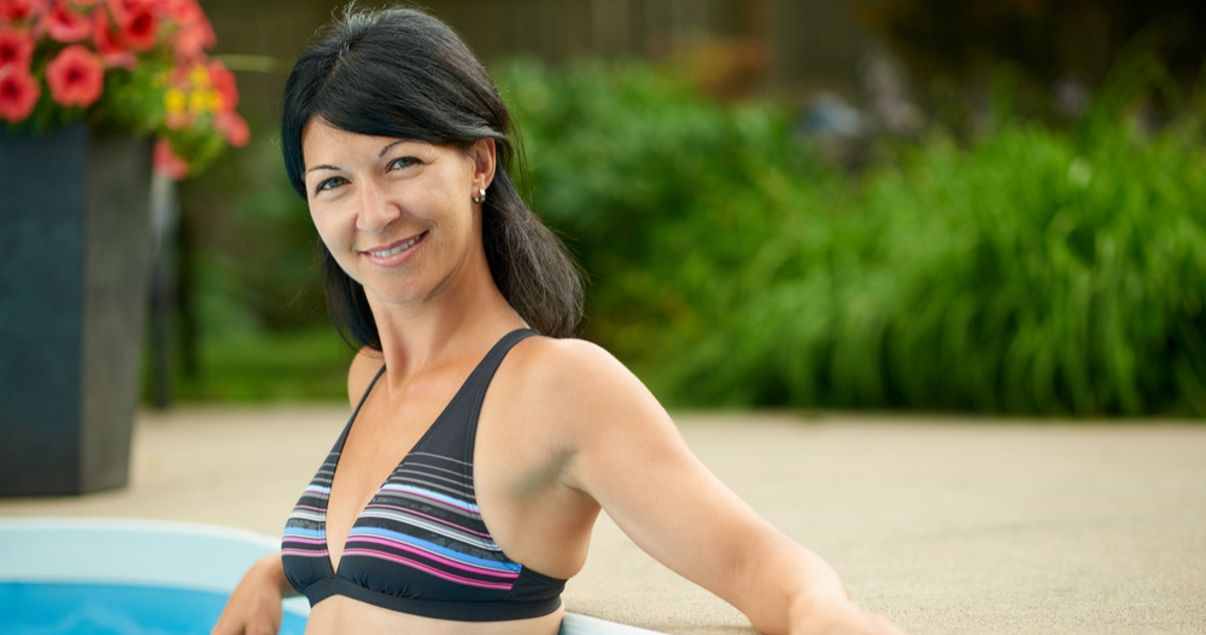 Middle aged black hair woman smiling in the pool not worrying about swimming with her hair system.