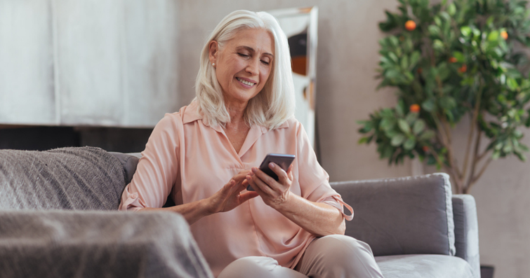 Mature woman using smartphone for buying wigs online