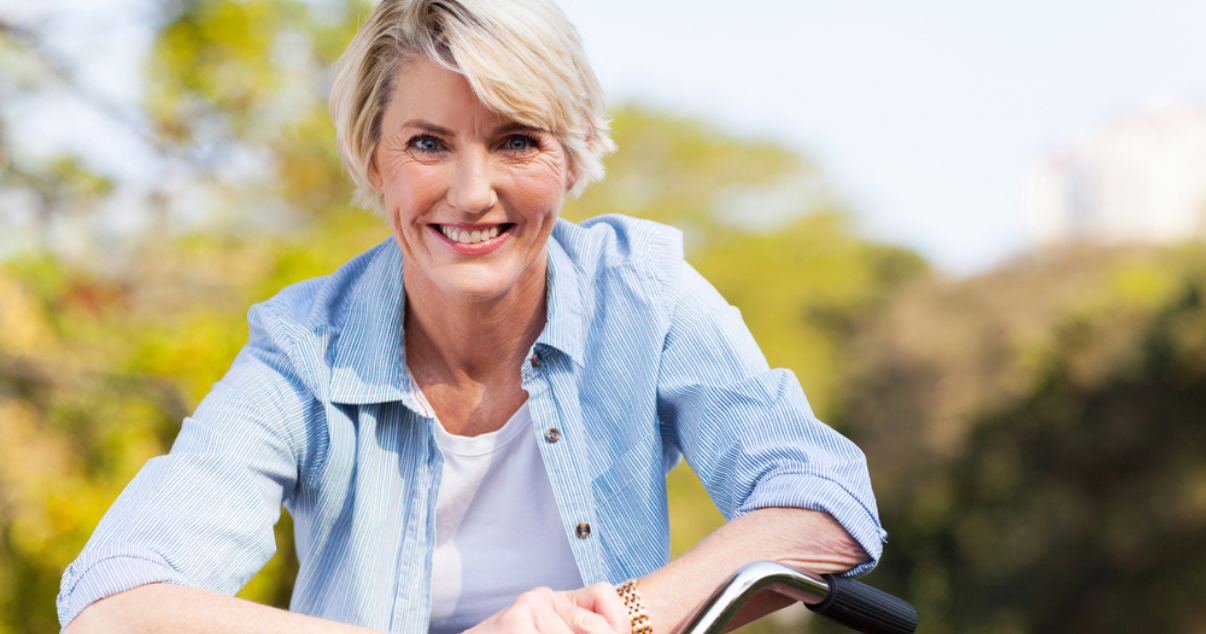 Middle age woman riding a bike with her custom hair system
