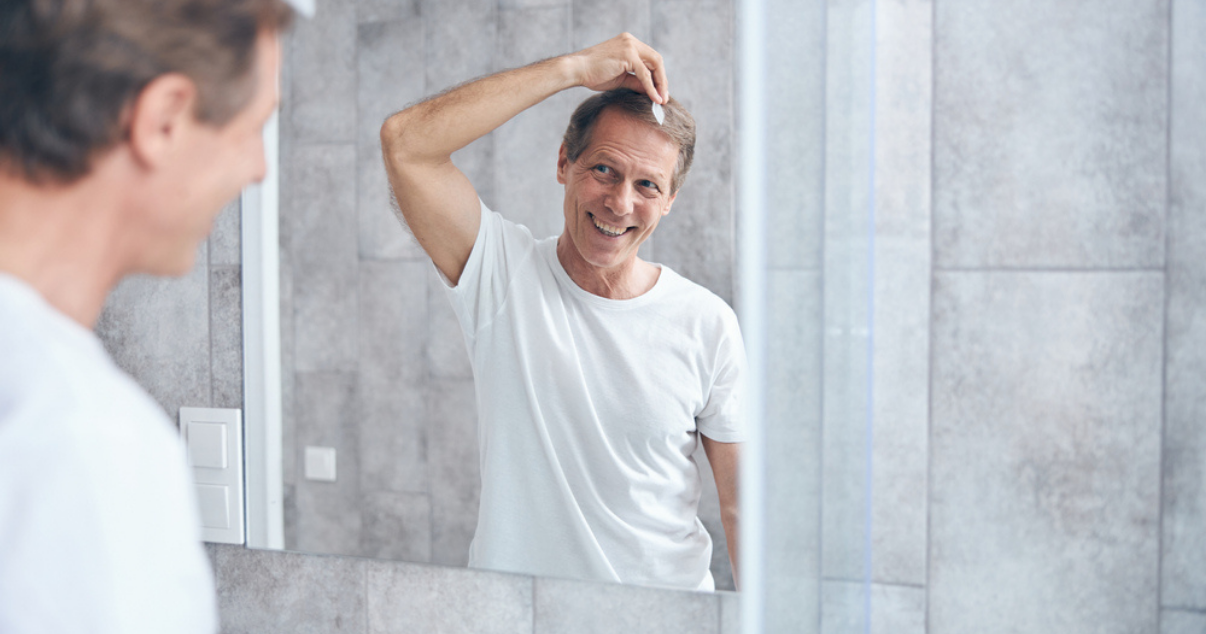 Older man doing hair system attachment at home without going to a hair studio