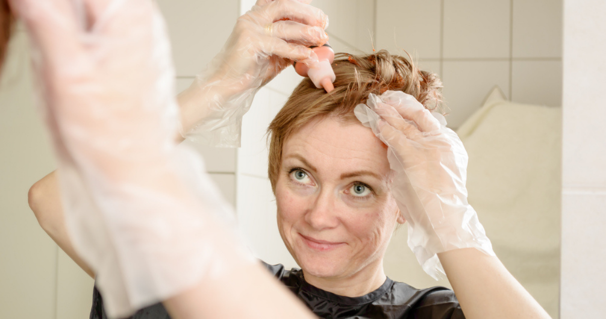 Woman dyeing hair system for hairpiece maintenance