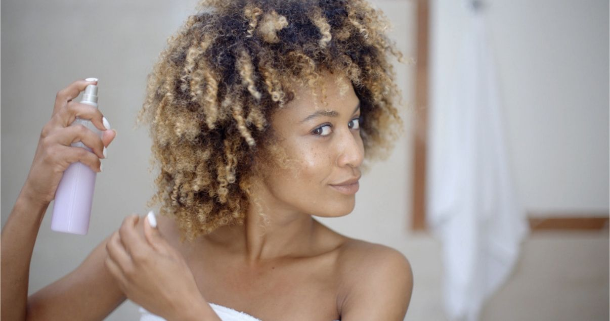 black woman spraying hair with styling tools
