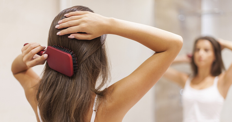 hair_system_maintence_brunette_women_brushing_long_hair_in_mirror