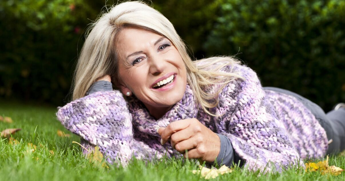 Middle aged woman laying on grass outdoors with her hairpiece with nice maintanence and odor