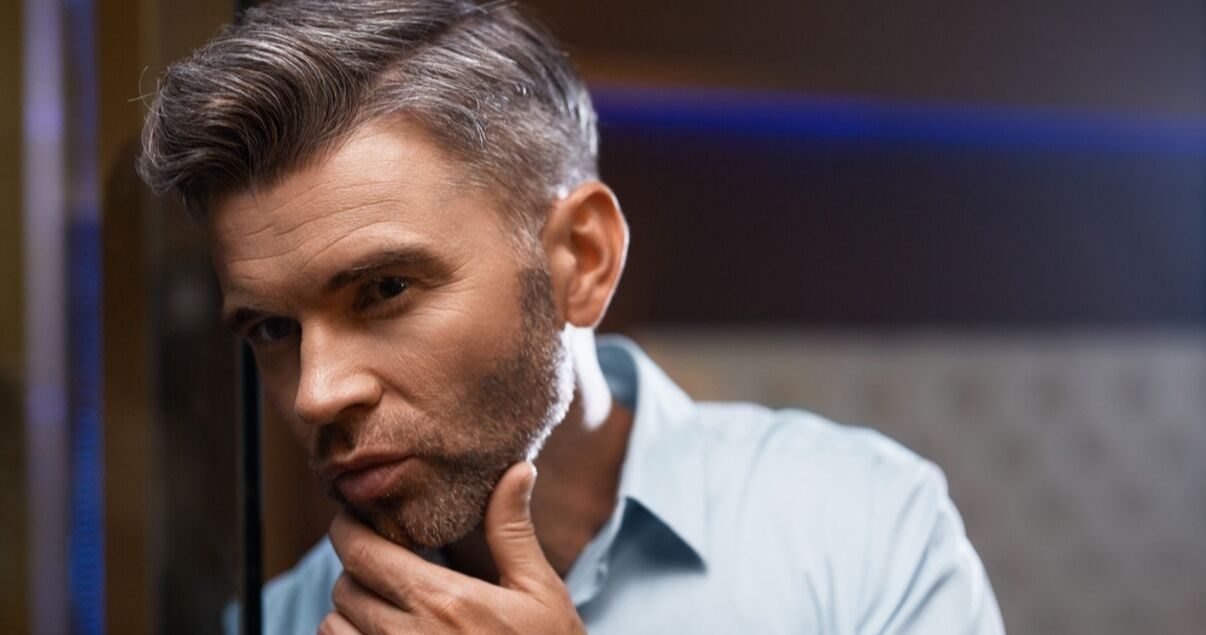 mature man with blue shirt and grey hair admiring hair style after washing hair system and styling it