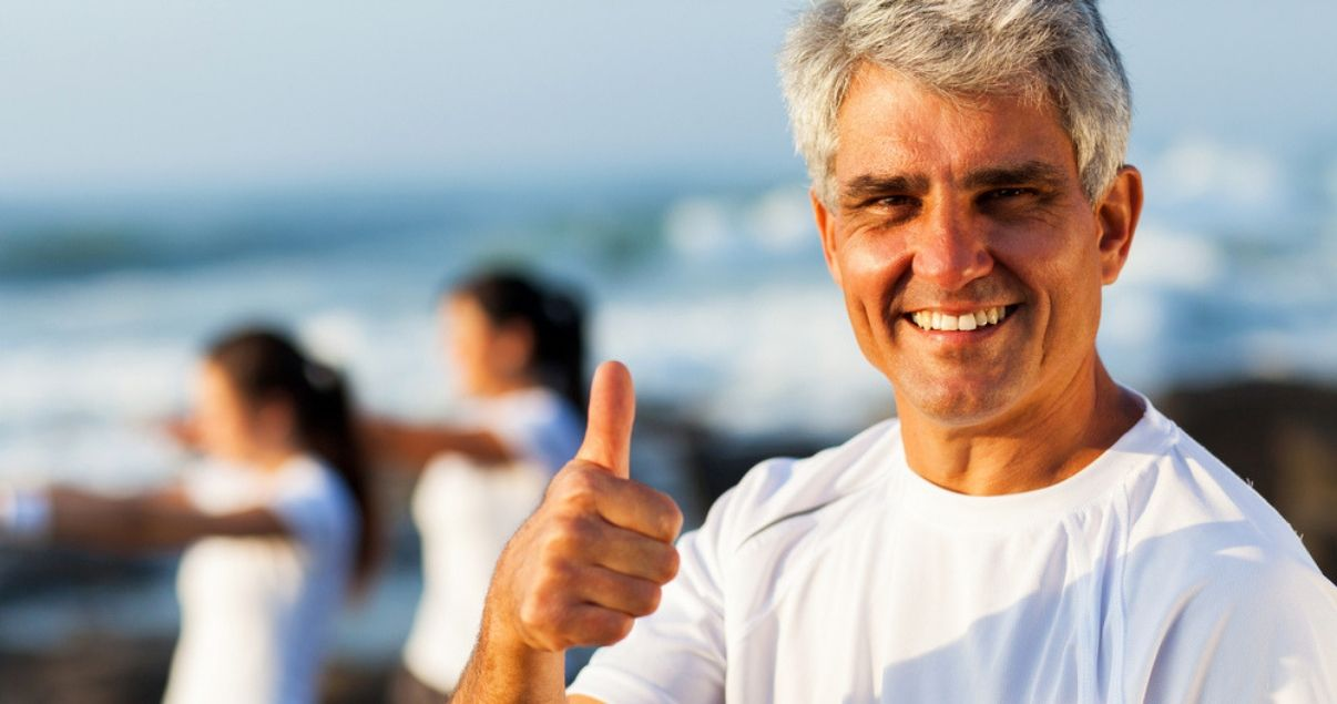 mature man with white shirt walking on the beach approving of his hair system bond after adhesive removal
