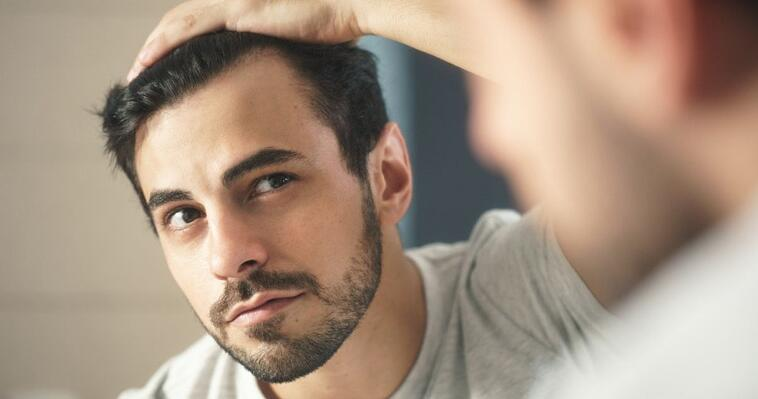 young man worried about hair loss looks at reflexion in mirror