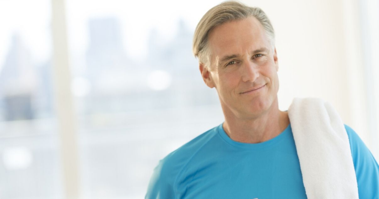 mature man working out with hair system in blue shirt