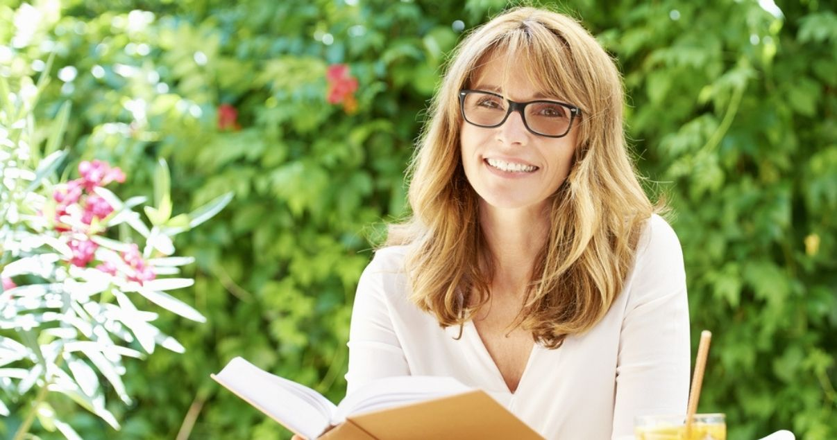 Smiling middle aged woman wearing best hair replacement system while reading