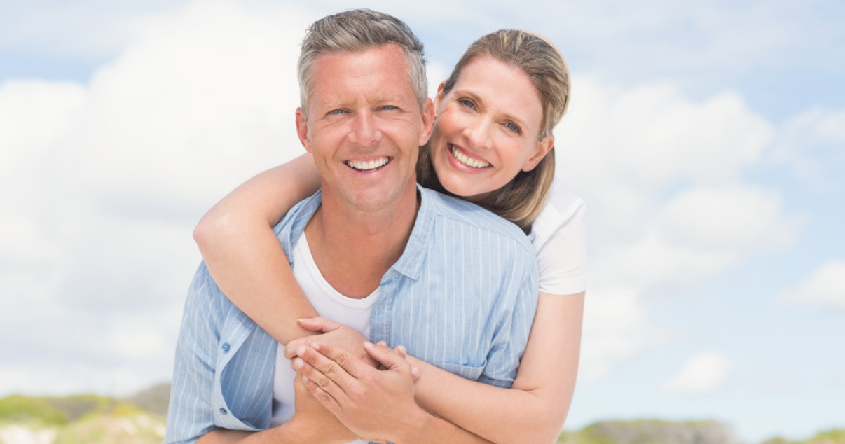 Couple enjoying the beach without worrying about hair damage from the sun