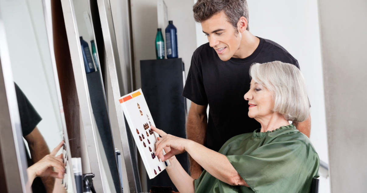 Mature woman looking at hair color chart for hairpiece maintenance